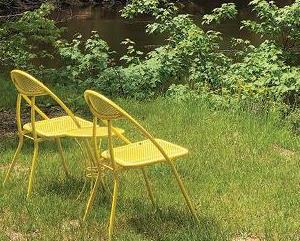 Yellow metal chairs sitting on bank of river in the upper peninsula in summer.