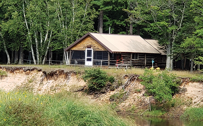 Brown log cabin on the river on summer day with green grass and plants covering the bank that the cabin overlooks.