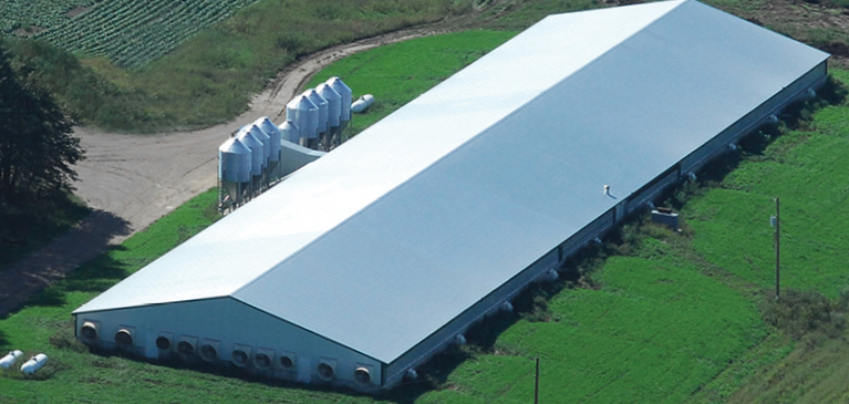 Bird's eye view of farm with long, new pole barn and holding tanks.