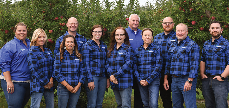 GreenStone Farm Credit Services fruit crop team standing in blue and black flannels in front of apples trees at a customer farm.