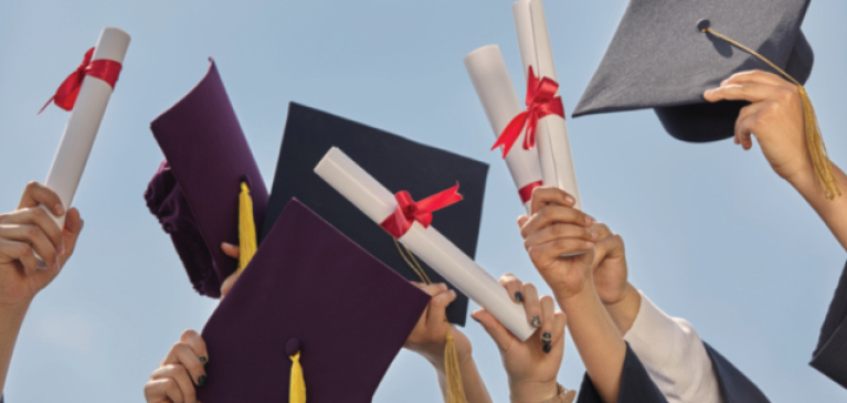 Students at graduation holding caps and diplomas