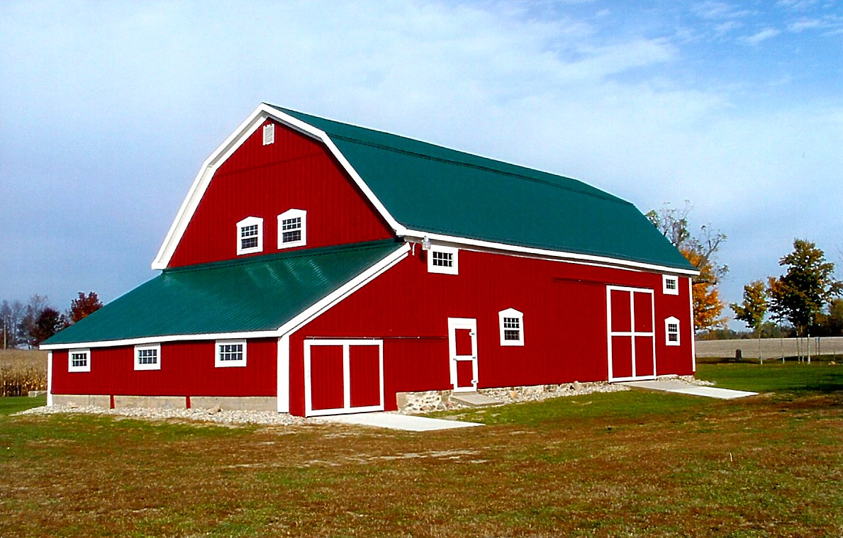Large red barn with green metal roofing completely redone on farm for barn believers fund