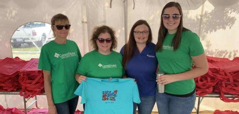 GreenStone employees pose for picture with blue t-shirt while setting up race for 5k run and walk.