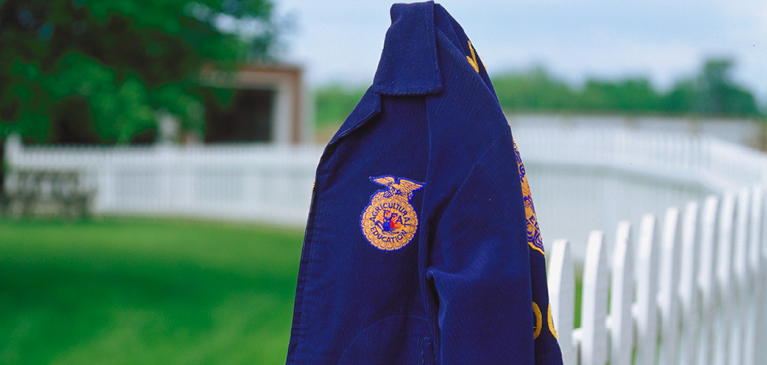 FFA blue jacket hanging on fence post in field