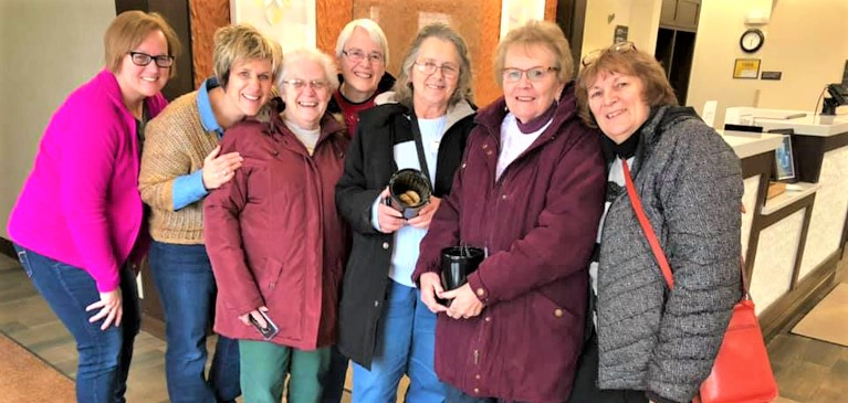 Group of farm women at annual Farm Women's symposium holding a cookie jar and smiling