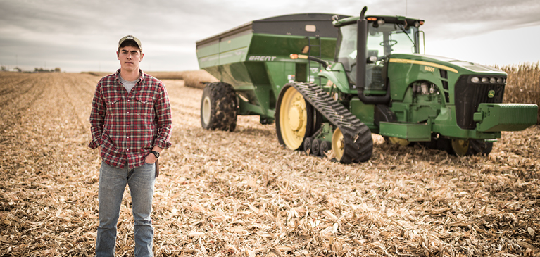 Farmer standing in front of field and combine tractor