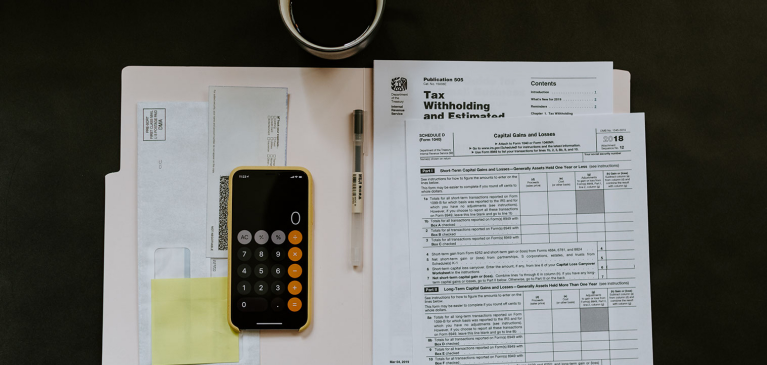 Tax papers on desk with calculator and coffee mug