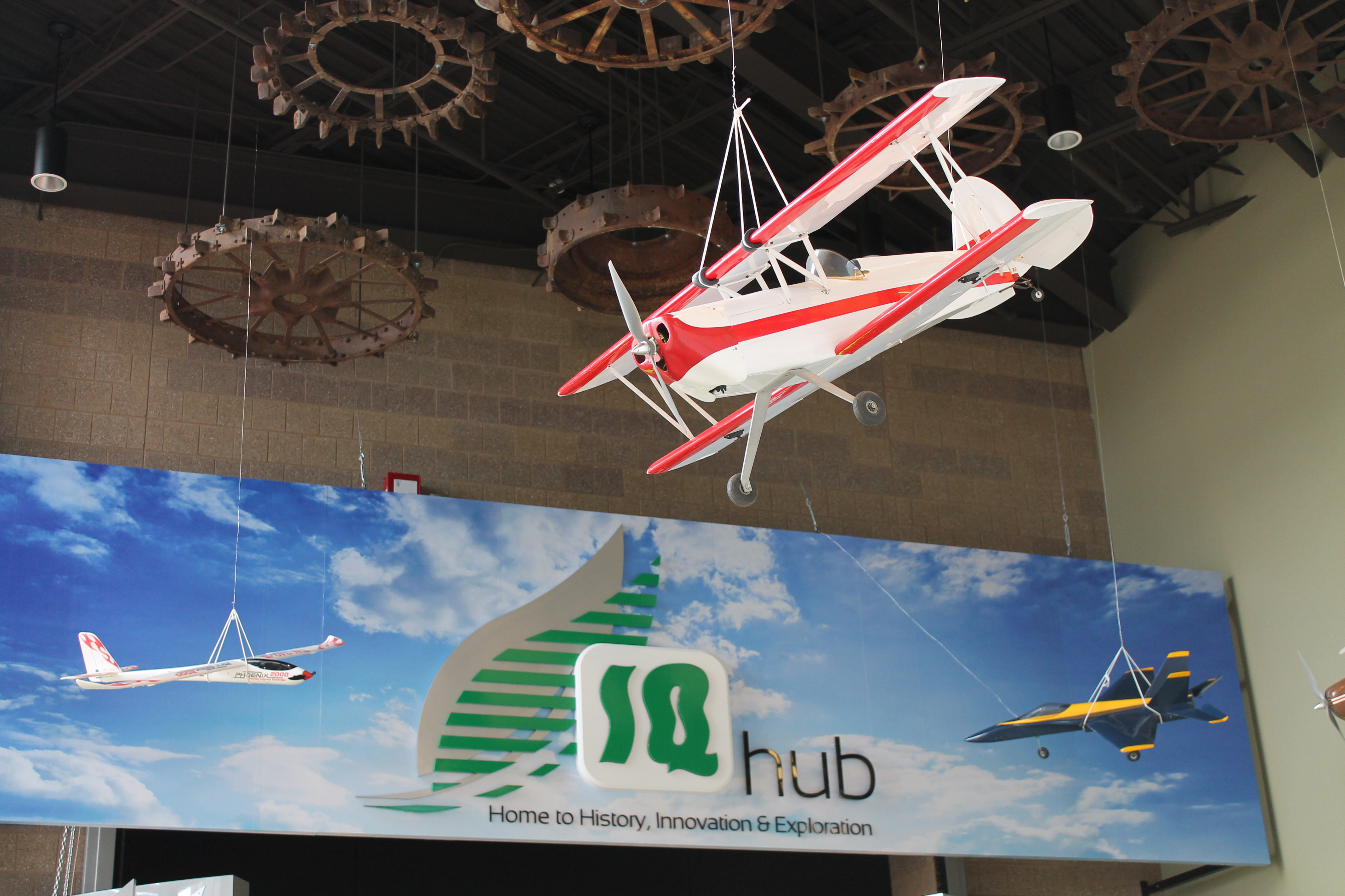 Large model airplane hanging from ceiling at AgroLiquid's IG Hub aviation exhibit.