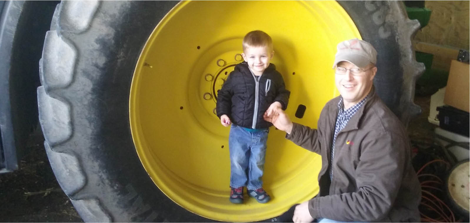 Farmer and his son by tractor tire