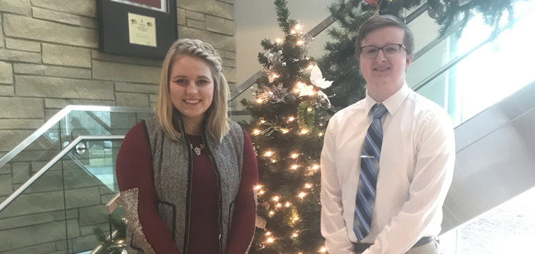 Amber Echlin and Jeffrey MacCowan standing by Christmas tree in GreenStone lobby