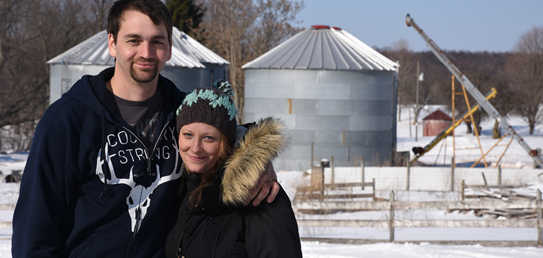 Michigan couple standing in front of oil drilling machines in snowy weather