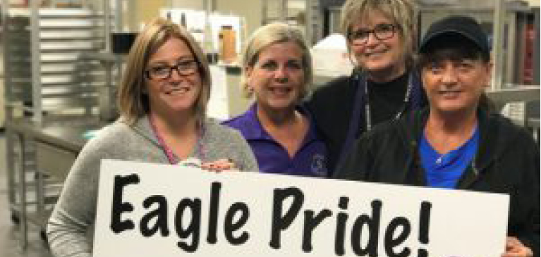 Schoolcraft lunch employees holding sign in cafeteria that says Eagle Pride