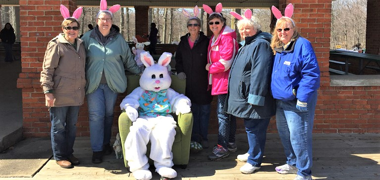 Women of the St. Johns Lioness Club standing under a pavilion at the annual Easter Egg Hunt with the Easter Bunny.