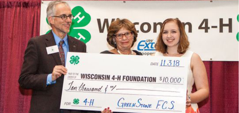 Three adults from Wisconsin 4H presenting a check