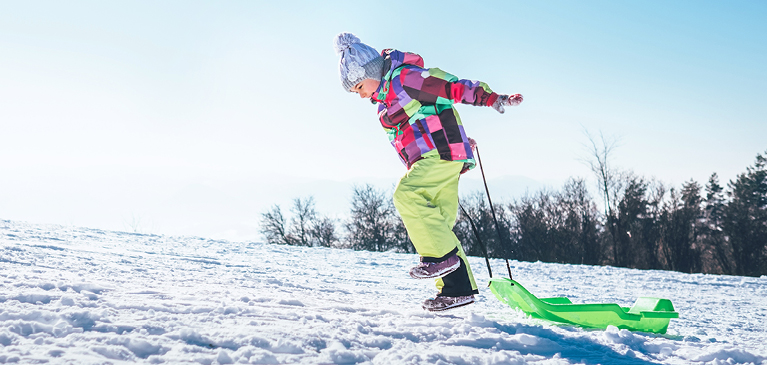 Young girl in colorful coat and green snowpants leaping while pulling plastic sled up snowy hillbank.