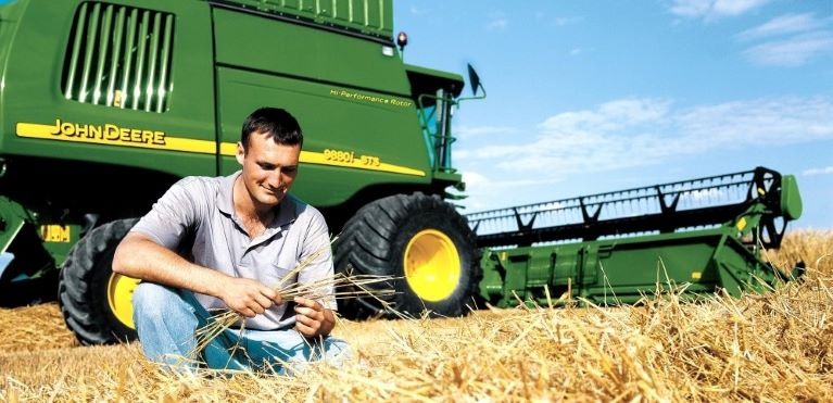 Young male farmer kneeling in front of John Deere combine in a hay wheat field during harvesting on sunny day