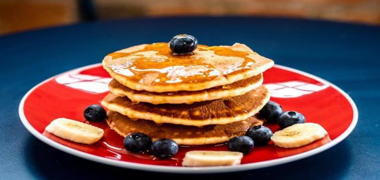 Blueberry pancakes stacked on red plate covered with syrup and butter