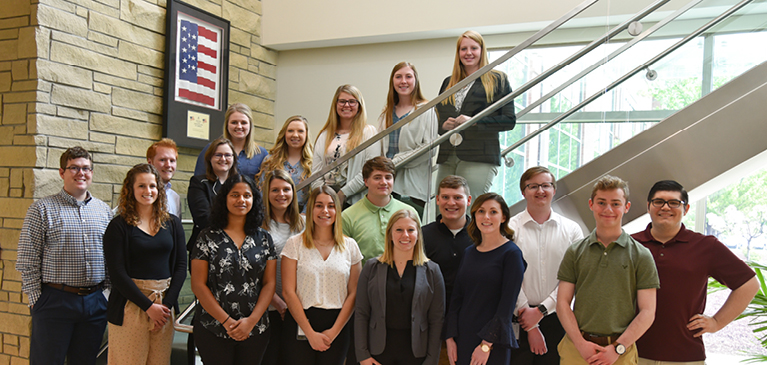 GreenStone's 2019 group of interns standing on stairs at the corporate office in East Lansing.