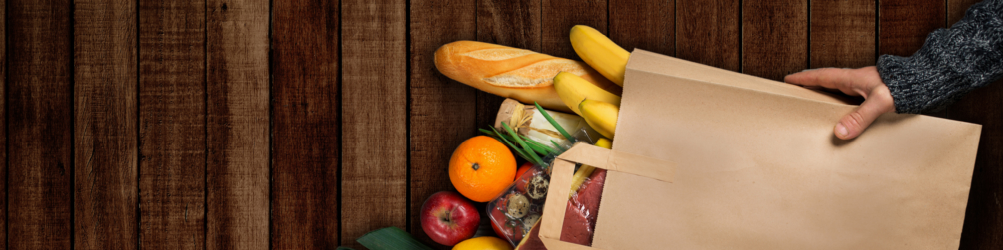 Grocery food items in paper bag on a wooded background